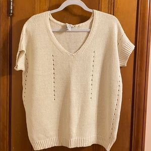 Short-sleeve cream-colored sweater.